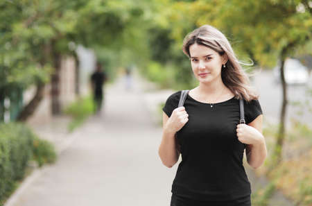 Fashion portrait of young stylish woman walking down the street, in trendy outfit, traveling with a backpack. High quality photo