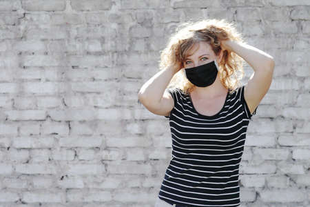 Portrait of a Girl in a protective mask free space for an inscription. Social distancing. White brick wall in the background. Reklamní fotografie