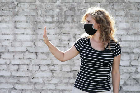Portrait of a Girl in a protective mask free space for an inscription. Social distancing. White brick wall in the background. Shows stop by hand Reklamní fotografie