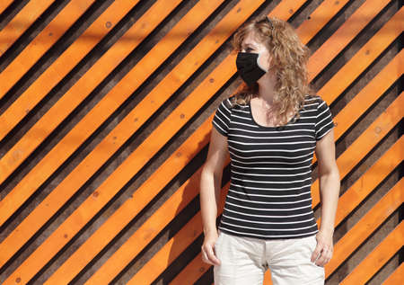 Portrait of a Girl in a protective mask free space for an inscription. Social distancing. Orange wooden wall in the background Reklamní fotografie