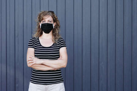 Portrait of a Girl in a protective mask free space for an inscription. Social distancing. Blue striped wall in the background