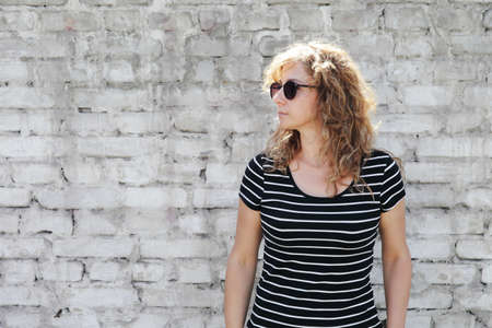 Woman portrait in sunglasses, free space for inscription. White brick wall in the background Reklamní fotografie
