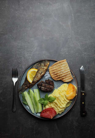 Fried fish, meat steak and vegetables on a plate. Concrete gray countertop. High quality photo