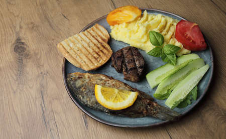 Fried fish, meat steak and vegetables on a plate. On a wooden table. High quality photo