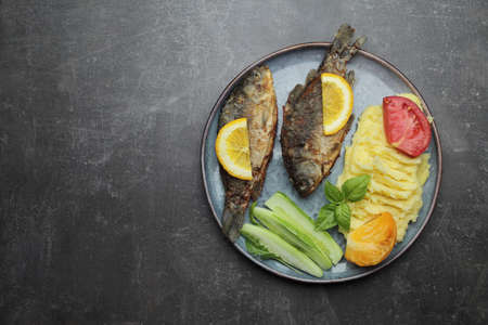 Fried fish and vegetables on a plate. Concrete gray countertop. High quality photo