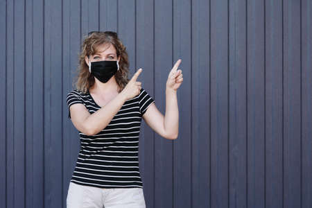 Portrait of a Girl in a protective mask, free space for text. Social distancing. Blue striped wall in the background Reklamní fotografie
