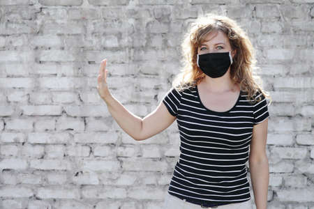 Portrait of a Girl in a protective mask, free space for text. Social distancing. White brick wall in the background. Shows stop by hand Reklamní fotografie