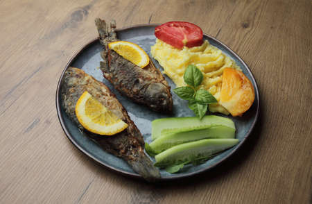 Fried fish and vegetables on a plate. On a wooden table. High quality photo