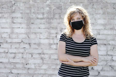 Portrait of a Girl in a protective mask, free space for text. Social distancing. White brick wall in the background.