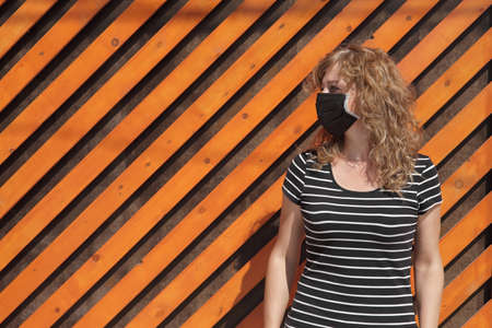 Portrait of a Girl in a protective mask, free space for text. Social distancing. Orange wooden wall in the background