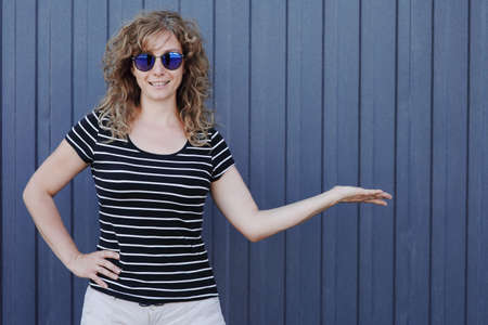 Woman portrait in sunglasses, free space for text. Blue striped wall in the background