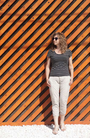 Woman portrait in sunglasses, free space for text. Orange wooden wall in the background Reklamní fotografie