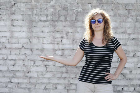 Woman portrait in sunglasses, free space for text. White brick wall in the background Reklamní fotografie