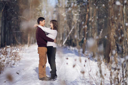 Young couple hug each other in winter in the park. Love story