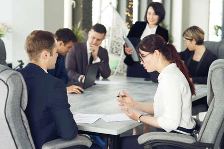 Group of young successful businessmen lawyers communicating together in a conference room while working on a project.