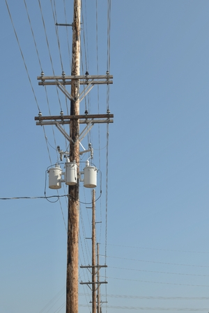 electric grid: Wooden power utility pole with transformers and cables.