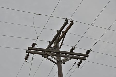 Houten elektriciteitspaal met transformatoren en kabels. Stockfoto
