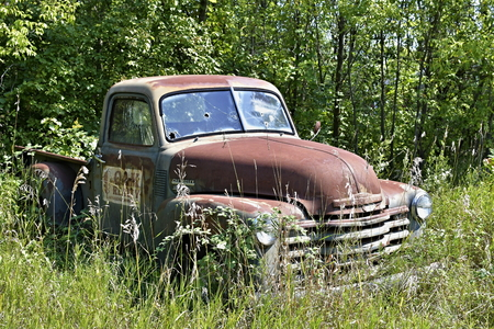disposed: Old abandoned Cheverolet pickup truck sitting in a field