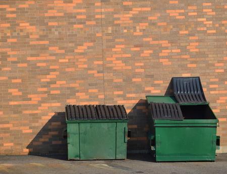レンガの壁のダンプスターをリサイクル グリーン