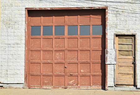 wooden garage door with small door Фото со стока