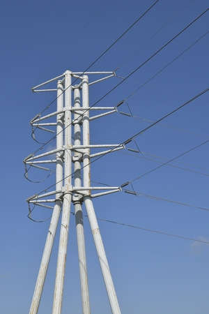 Electricial Transmission Tower with multiple cables bright blue sky Stockfoto