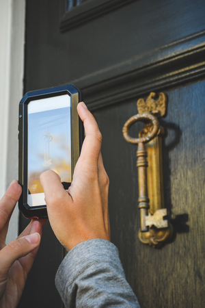 2 hands holding a mobile phone photographing a door knocker