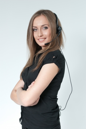 steadfast: Sexy smilling call center operator. Girl wearing headset standing on uniform background. One of a series. Business collection. Stock Photo