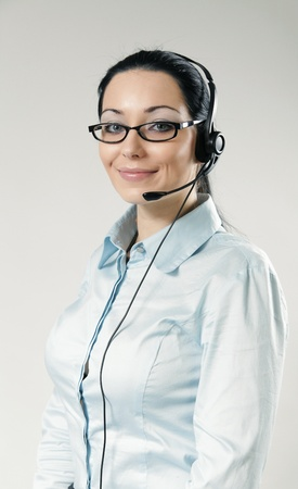Sexy smiling call center operator portrait. Sexy girl wearing headset and glasses standing on uniform background. One of a series. photo