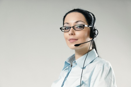 Sexy smiling haughty call center operator portrait. Sexy girl wearing headset and glasses standing on uniform background. One of a series. photo