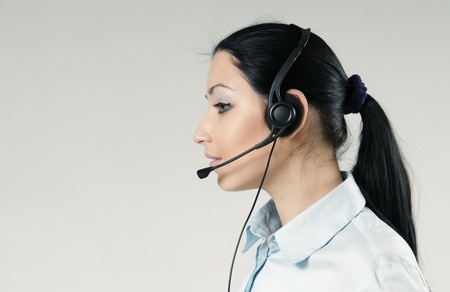 Attractive call center operator portrait. Sexy girl wearing headset standing on uniform background. One of a series. photo