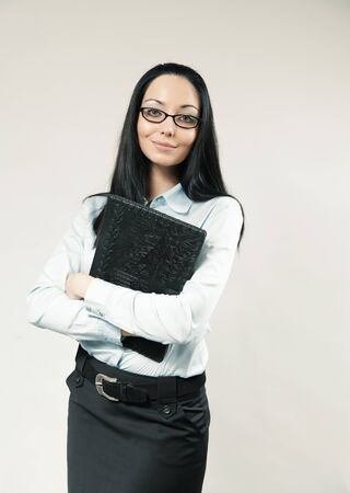 Happy business woman  assistant  secretary portrait. Girl clasping folder to breast. Wearing shirt, skirt and glasses. One of a series. Banco de Imagens