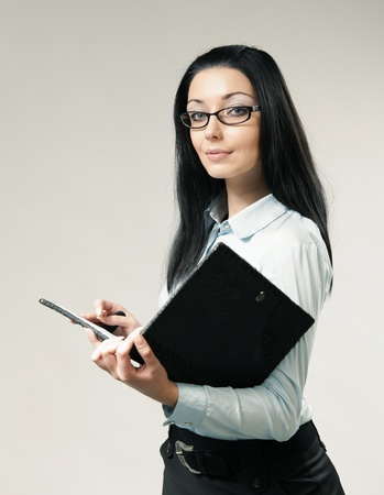 Sexy brunette businesswoman  assistant  secretary portrait. Girl holding leather folder. Wearing shirt, skirt and glasses. One of a series.