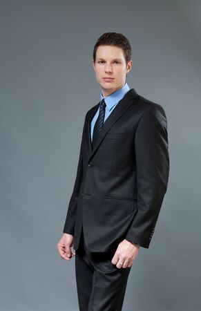 Young businessman wearing classic dark suit. Half-turn studio shot. One of a series. Stock Photo - 9056596