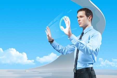 Young handsome businessman using futuristic hologram interface and keyboard in the bio style interior.