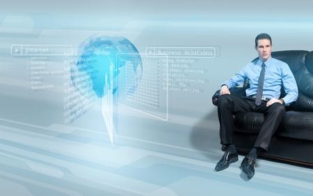 holographic: Giovane imprenditore bello seduta sul divano analizzando i dati dallo schermo di interfaccia virtuale olografica.