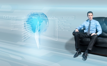 holograph: Young handsome businessman sitting on the sofa analyzing data from virtual holographic interface screen.