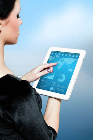 Cute brunette using interface of new touch pad device  Stylish modern icons, world map and infographics on the screen  Future lifestyle collection  Stock Photo