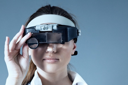 Young female doctor wearing magnifying glass equipment on her had  Medical   pharmaceutical research concept  Healthcare collection  photo