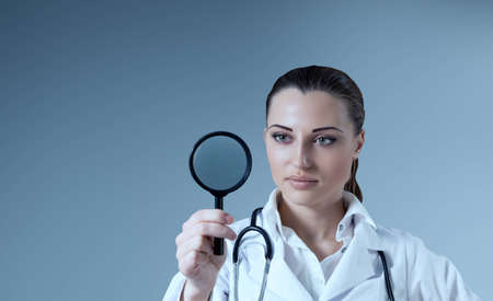 Young female doctor holding magnifying glass in right hand  Empty space to place your logo   text   product  Medical   pharmaceutical research concept  Healthcare collection  photo