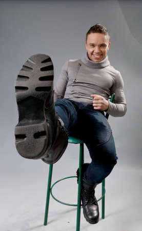 Sexy smiling fit and neat young man in studio playing the fool  Wearing grey turtleneck sweater, dark blue jeans and black boots  Sitting on green bar chair  Fit and neat collection  Stock Photo - 12897601