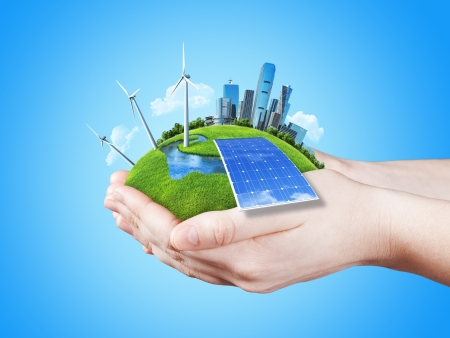 seedling growing: Hands holding clear green meadow with sun battery block, wind mill turbines and city skyscrapers  Concept for ecology, growing business, freshness, freedom and other lifestyle issues  Green fields collection