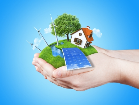 Hands holding clear green meadow with sun battery block, wind mill turbines and countryside house  Concept for ecology, alternative energy, freshness, freedom  Green fields collection  photo