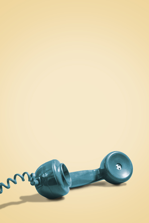 Vertical image of retro green rotary phone handset on a vintage yellow background with copy space and room for text
