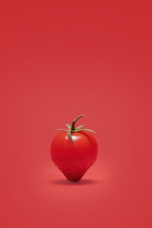 Abstract cherry tomato combined with a strawberry on a red background