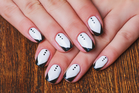 nail care: Black and white  nail art on dark wooden background
