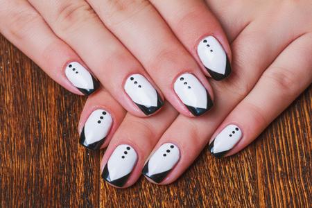 Black and white  nail art on dark wooden background