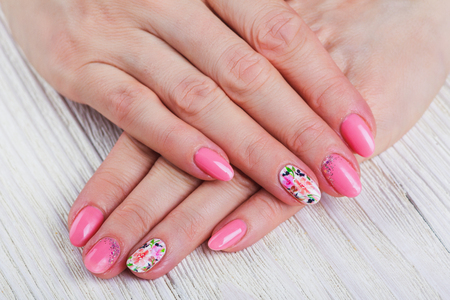 naildesign: Light pink nail art with printed flowers on white background Stock Photo