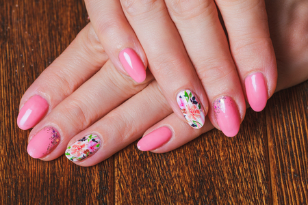 Light pink nail art with printed flowers on wooden background
