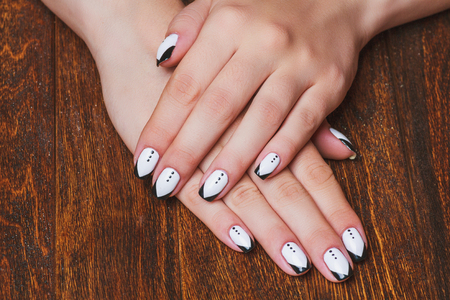 nails: Black and white  nail art on dark wooden background