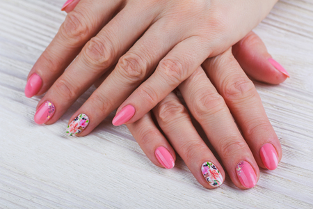 Light Pink Nail Art With Printed Flowers On White Background Stock